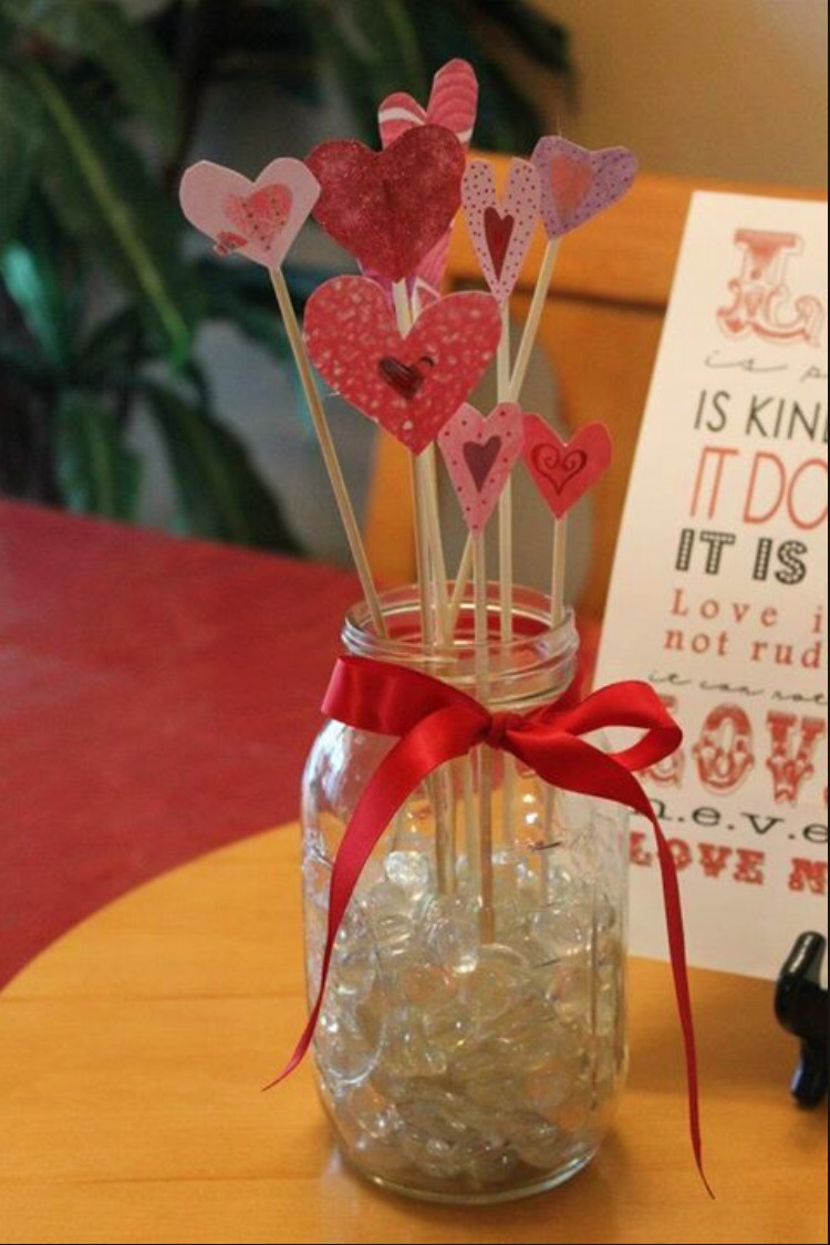 make a diy flower vase cut out cardstock hearts and glue them to wooden skewers place them in a mason jar filled with clear rocks: day orchid decor